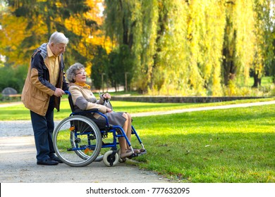 old couple in the park - woman sitting on a wheelchair and man standing behind