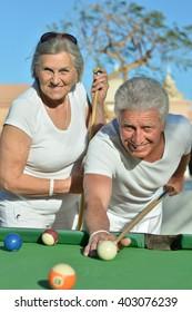 old couple playing billiard
