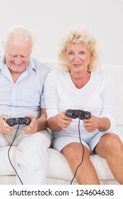 Old couple playing video games sitting on the sofa