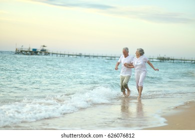 Old couple running on sea beach