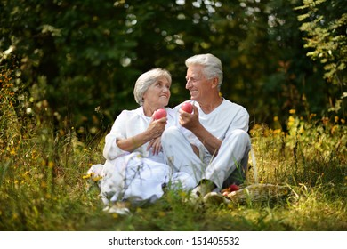 old couple sitting in grass in forest and eating apples