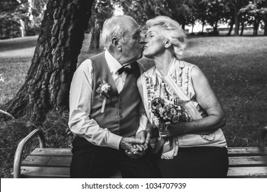 Old couple is sitting on bench in green park. Grandmother and grandfather at golden wedding anniversary celebration. Fifty years together. Romantic elderly is kissing and hugging. Black and white.