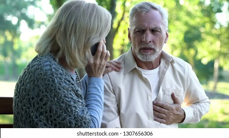 Old couple sitting on bench, man suffering arrhythmia, wife calling emergency