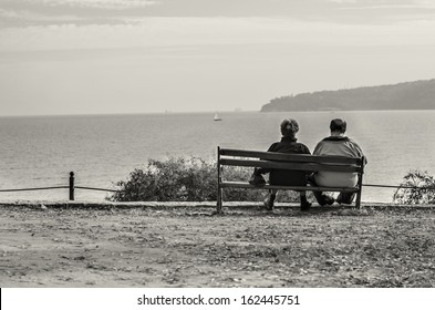 old couple sitting on bench watching the ocean