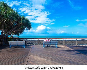 an old couple sitting on a park bench cuddling looking at the beautiful ocean and sky.