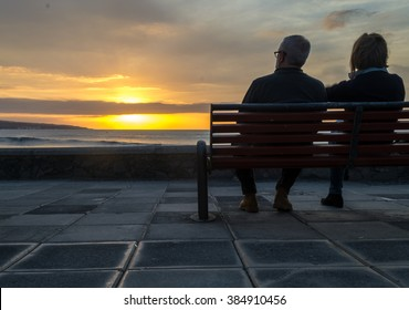 Old couple waiting for colourfull sunset on the bench near ocean
