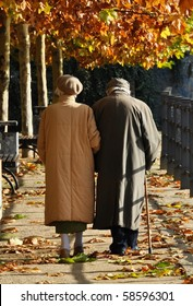 Old couple walking along an autumn path arm in arm
