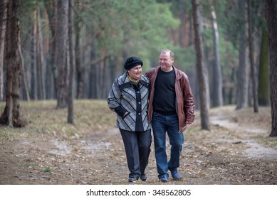 old couple walking in the forest