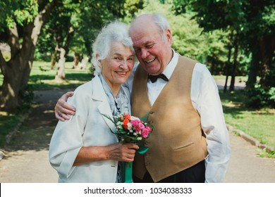 Old couple is walking in the green park. Grandmother and grandfather at their golden wedding anniversary celebration. Fifty years together love story of elderly people. Grandma and grandpa laughing.