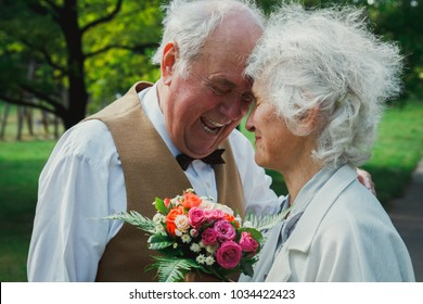 Old couple is walking in the green park. Grandmother and grandfather at golden wedding anniversary celebration. Grandma and grandpa laughing and hugging. Fifty years together romantic love story.