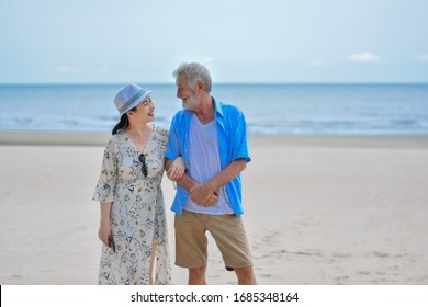old couple walking on beach. sweet on beach. lovely concept. Beautiful Asian senior couple walking at tropical beach. With copy space