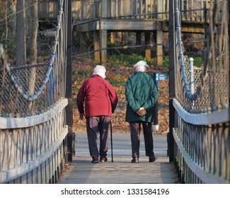 Old couple walking on bridge