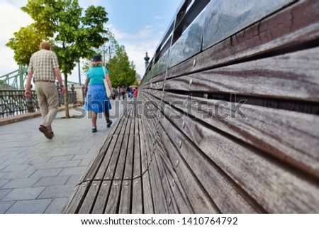 Old couple walking together near the Danube river in Budapest, Hungary. Empty benches near the Liberty bridge after a rainy spring day.