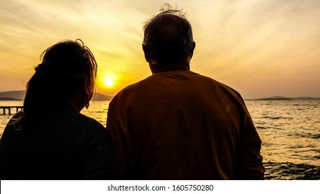 Old couple watching beautiful sunset on shore. Feelings, happy retirement lifestyle. Romantic senior man & woman enjoying now, today. Seize the day moment. Wallpaper picture of two 60s person together