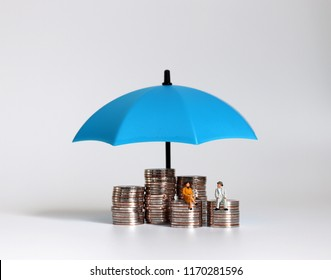 The old couples miniatures sitting on a pile of coins and umbrellas.