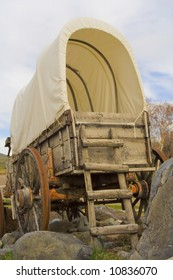 An old covered wagon sits on a rocky patch of ground.