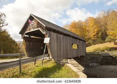 Old covered wooden bridge with an American flag in Vermont, countryside