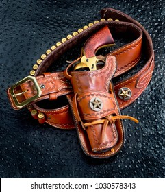 Old cowboy 45 pistol and leather tooled holster.