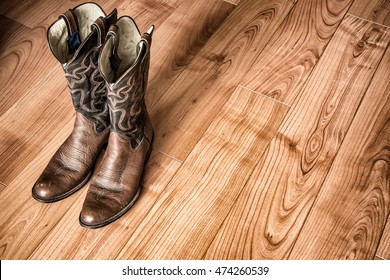 Old Cowboy Boots on Wood Floor. Pair of old western cowboy boots sitting on a hardwood floor.