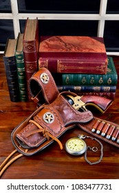 Old cowboy gun in holster with pocket watch and literature.