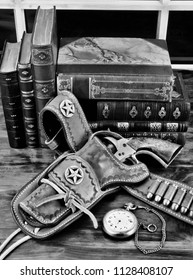 Old cowboy gun in holster with pocket watch and literature in black and white.