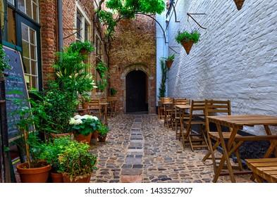 Old cozy narrow street with tables of restaurant in historic city center of Antwerpen (Antwerp), Belgium. Night cityscape of Antwerp. Architecture and landmark of Antwerpen