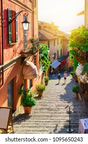 Old cozy street in beautiful Bellagio, Como lake, Italy. Architecture and landmark of Bellagio at sunset. Scenic alley.