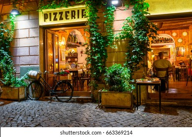 Old cozy street at night in Trastevere, Rome, Italy. Trastevere is rione of Rome, on the west bank of the Tiber in Rome, Lazio, Italy.  Architecture and landmark of Rome.