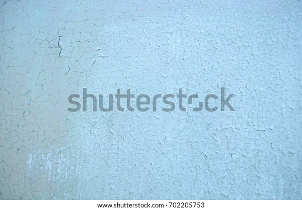 Old Cracked Blue Paint on a Wall Surface. Peeling Paint Texture. Pattern of Cracks on the Wall. Abstract Background. Grunge Texture. Close-up