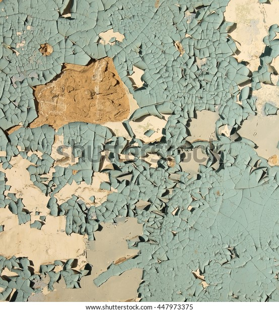 old cracked paint. / Old cracked paint blue on top of a white wall, in some places completely flown away, side lighting sunlight