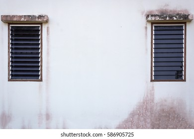 Old cracked wall with a window on background