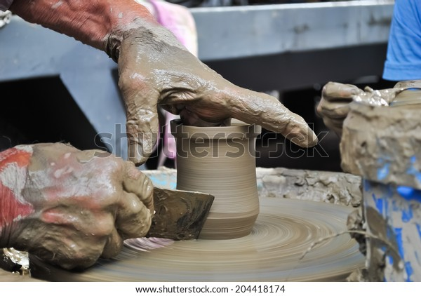 Old craftsman working on a clay pot