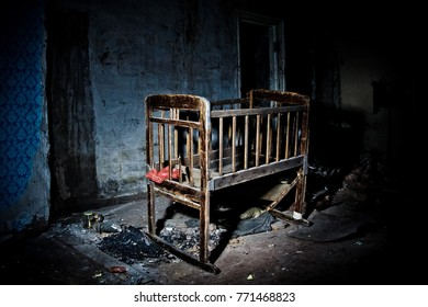 Old creepy eerie wooden baby crib in abandoned house. Horror concept.