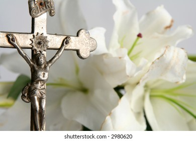 Old cross on white easter lilies background