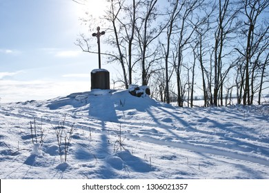 Old cross in the winter landscape.