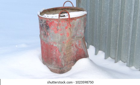 Old crumpled barrel in the snow.