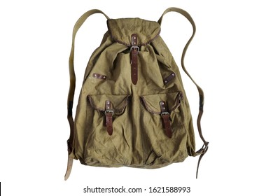 Old crumpled dirty vintage army military or travel backpack, made of khaki color camouflage tarpaulin fabric, isolated on a white background. Worn retro knapsack with some stains. Closeup. Copy space