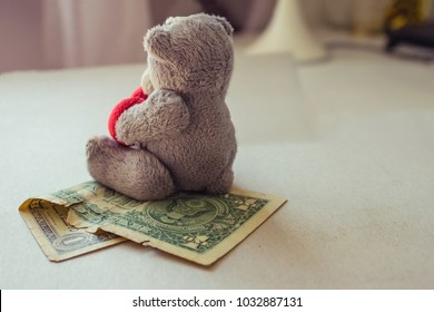 An old, crumpled dollar and a small children's toy. Expenses for children, alimony, children's pocket money. The background is blurred. A toy of mass production.