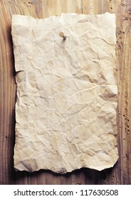 Old crumpled paper is on a wooden wall