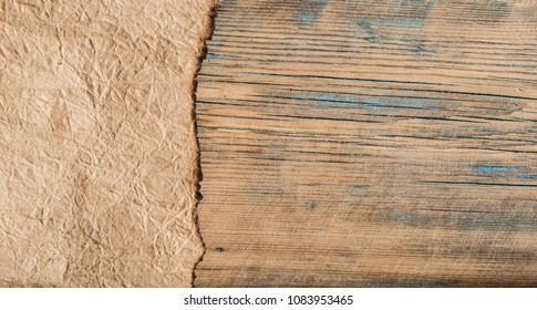 Old crushed paper with the burned edges over wood background