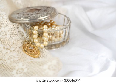 An old crystal jewelry box with the aged silver lid off contains strands or pearls and a gold and diamond locket. All items are on soft cotton and delicate lace fabric in white and ivory. Copy space.