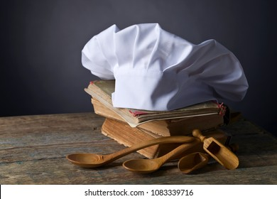 Old culinary books , chef hat and wooden spoons . Kitchen accessories on the old wooden table .