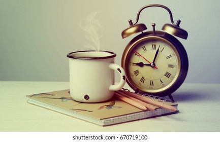 An old cup of coffee and an alarm clock on a wooden table.