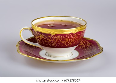 An old cup filled with hot drink for tea