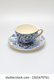 Old cup with floral decoration on white background