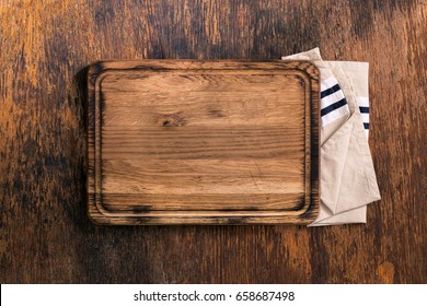 Old Cutting Board with cloth napkin on a old wooden table, top view