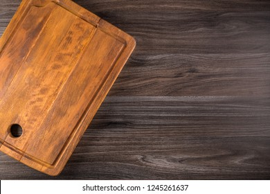 Old cutting board on dark background, top view. Flat lay.
