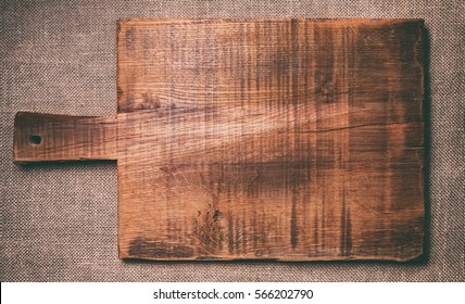 Old Cutting Board on dark fabric background. Toning