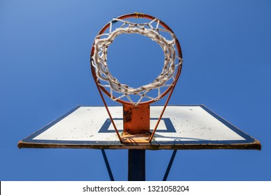 Old and damaged basketball hoop and net seen from below. Sunny day with blue sky.