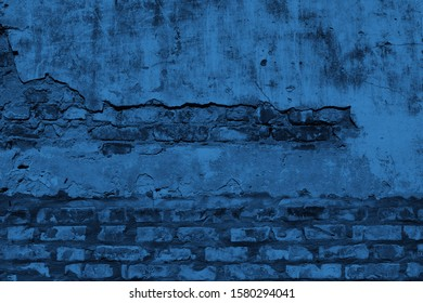 Old damaged  brick blue wall with shabby plaster. Empty old brick wall texture. Grunge blue  color stonewall background. Color of the year 2019. Main trend concept.
